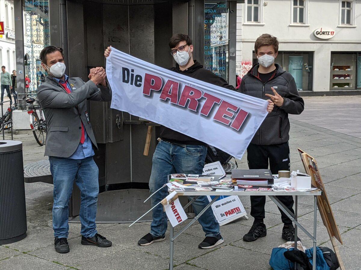 Sven Sonnhalter, Denis Schröder und Andrej posieren mit der PARTEI-Fahne